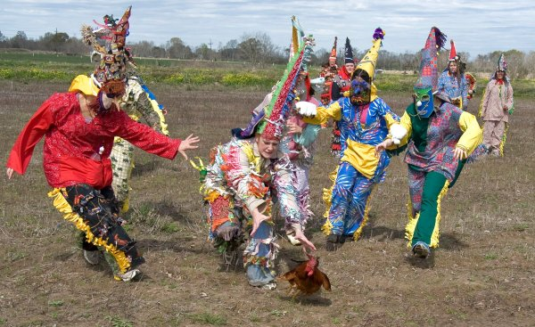 Los Mardi Gras persiguiendo un pollo, una de las imágenes habituales del Courir de Mardi Gras