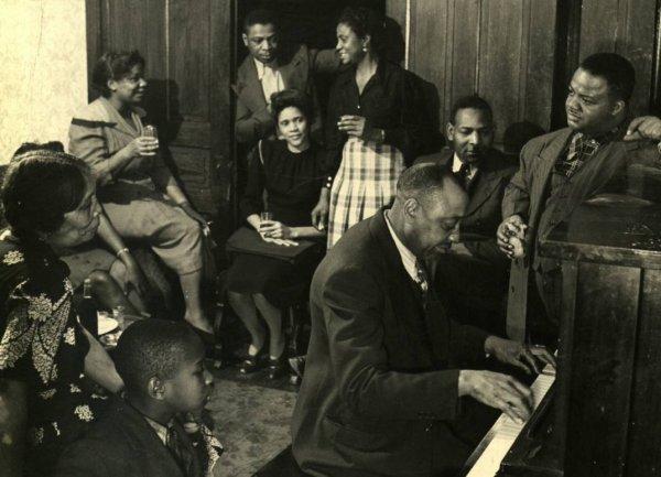 Meade Lux Lewis, apoyado en el piano, escuchando a su maestro Jimmy Yancey